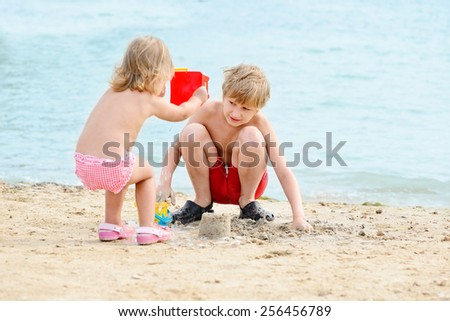 brother and sister playing sand on the beach - stock photo