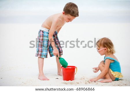 Brother and sister playing together on tropical beach by ocean shore - stock photo