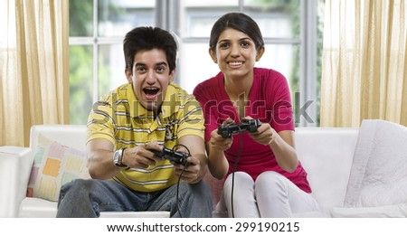 Brother and sister playing video games - stock photo