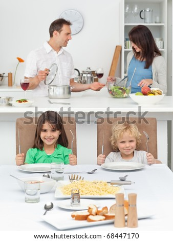 Brother and sister playing with forks while their parents cooking in the kitchen - stock photo