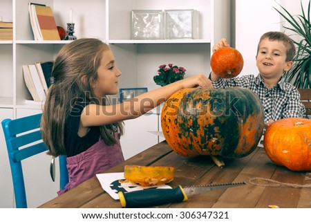 Brother and sister playing with pumpkin on Halloween night. Selective focus and small depth of field. - stock photo