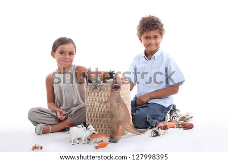Brother and sister playing with toy animals - stock photo