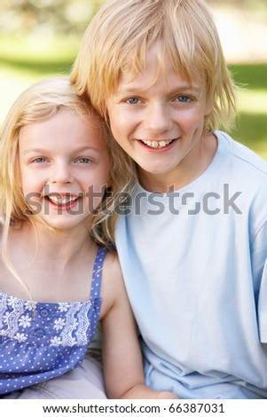 Brother and sister pose in a park - stock photo
