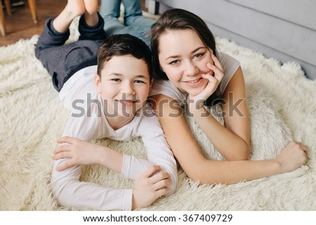 Brother and sister pose, smiling while lying on the floor at home