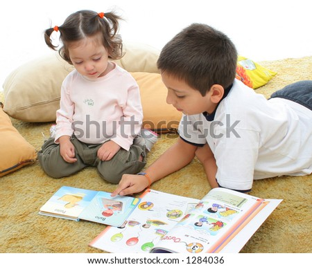 Brother and sister reading books over a carpet. They look interested and concentrated. Visit my gallery for more images of children - stock photo