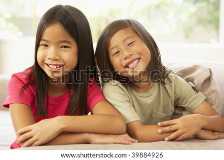 Brother And Sister Relaxing On Sofa At Home - stock photo