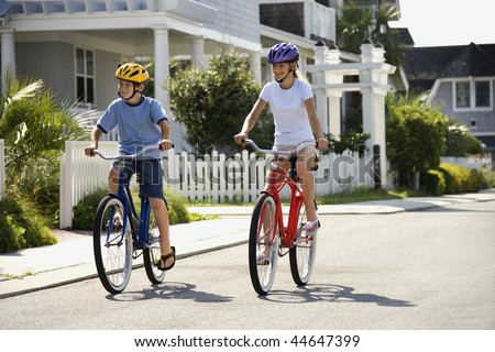 Brother and sister riding bikes together on street.  Horizontally framed shot. - stock photo
