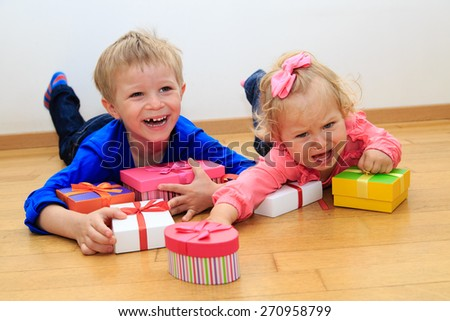 brother and sister rivalry concept, sorting presents - stock photo