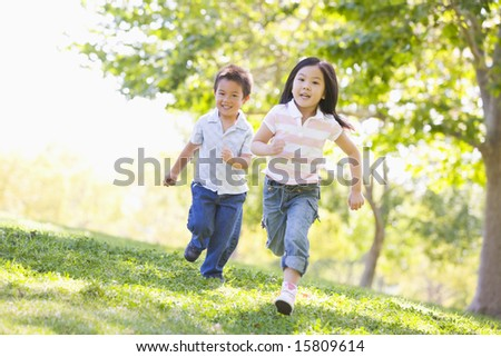 Brother and sister running outdoors smiling - stock photo