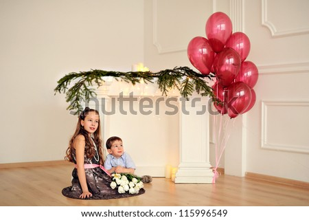 Brother and sister's birthday. Happy children around the fireplace. Balloons. - stock photo