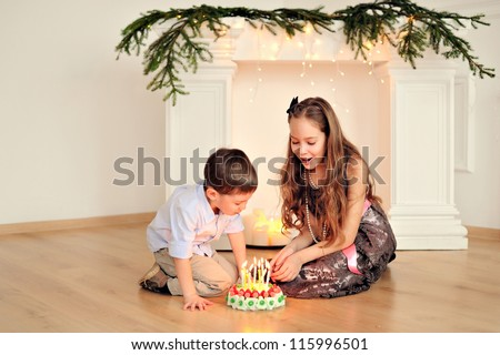 Brother and sister's birthday. Happy children at the fireplace