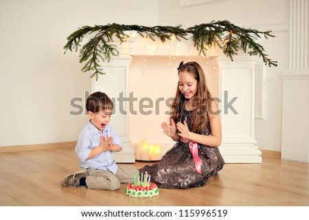 Brother and sister's birthday. Happy children at the fireplace - stock photo