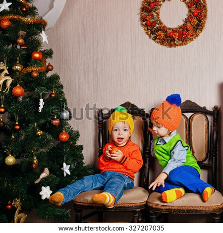 Brother and sister share the apples sitting on a chair near Christmas tree. Cute little kids. Happy family and Merry Christmas. - stock photo