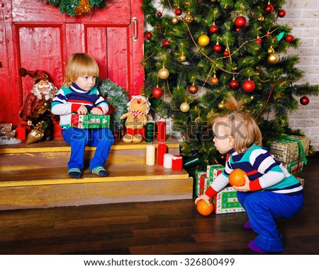 Brother and sister share the gifts near a Christmas tree. Cute little kids. Happy family and Merry Christmas. - stock photo