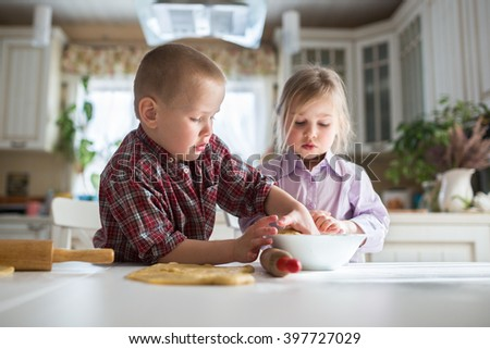 brother and sister siblings children preparing cookies in the kitchen,  large family. casual lifestyle photo series in real life interior - stock photo