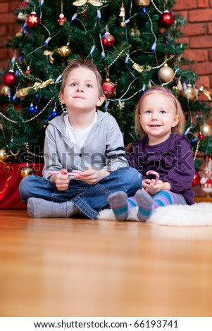 Brother and sister sitting near beautiful Christmas tree - stock photo