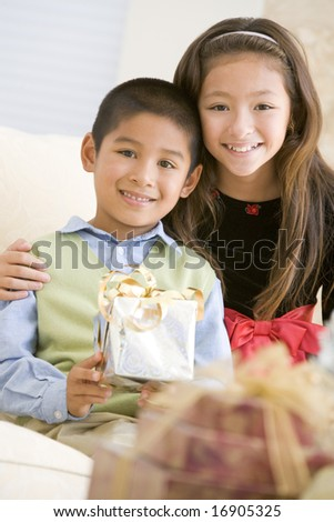 Brother And Sister Sitting On Couch Holding Christmas Gift - stock photo