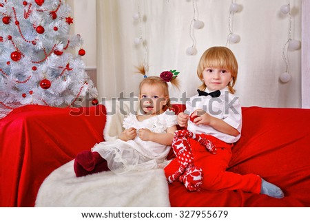 Brother and sister sitting on the couch near Christmas tree. Cute little kids. Happy family and Merry Christmas. - stock photo