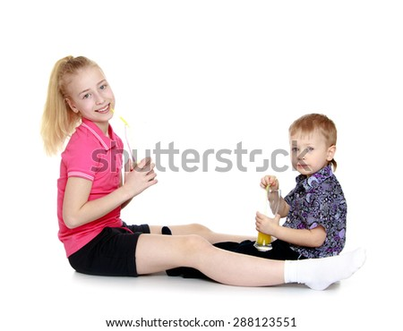 Brother and sister sitting opposite each other and drink from glasses of orange juice-isolated on white background - stock photo