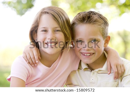 Brother and sister sitting outdoors smiling - stock photo