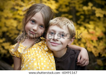 Brother and sister sitting outside - stock photo
