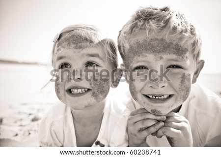 Brother and sister smile at the camera, brightly lit, on the beach, faces covered in sand. - stock photo