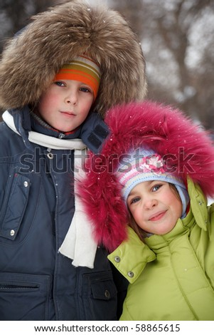 Brother and sister smiling looking into camera in winter forest, in jackets with fur hoods on their heads. - stock photo