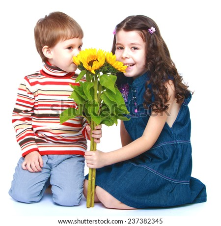 Brother and sister sniffing bouquet of yellow flowers.Isolated on white background portrait. - stock photo