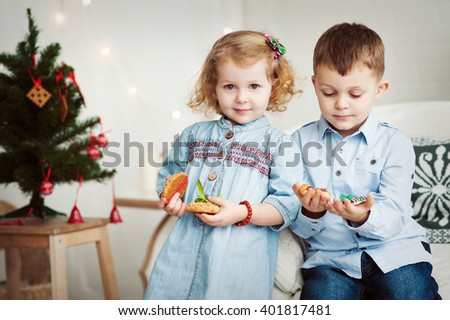 Brother and sister stand near decorated Christmas tree and holding holiday cookies. - stock photo