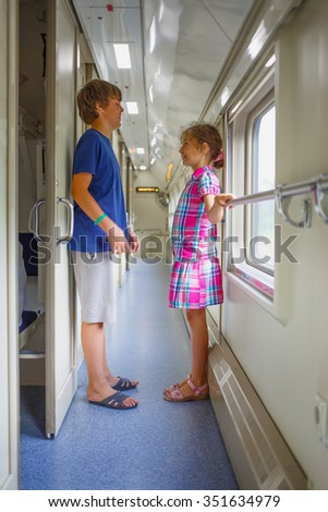 Brother and sister standing in corridor train compartment and laughing - stock photo