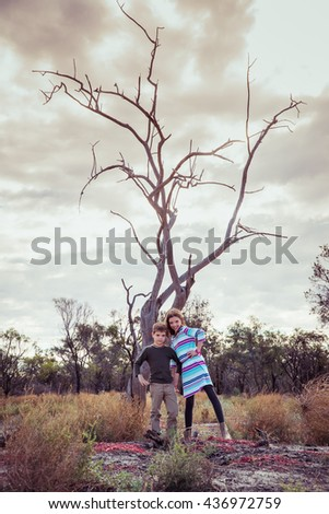 Brother and sister standing in front of an old tree in outback Australia - stock photo