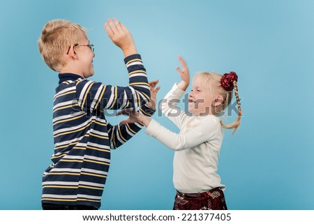 Brother and sister start a playful fight with each other.  - stock photo