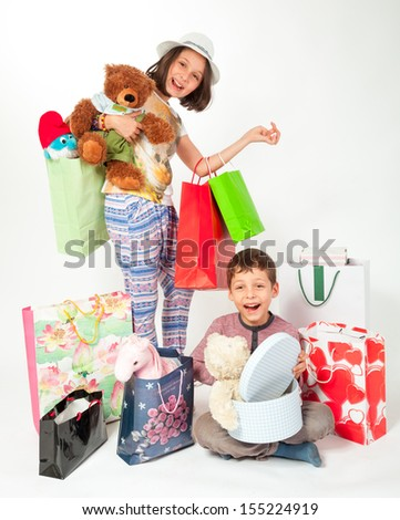Brother and sister surrounded by gifts, happy - stock photo