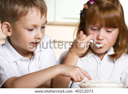 Brother and sister taste cream - stock photo