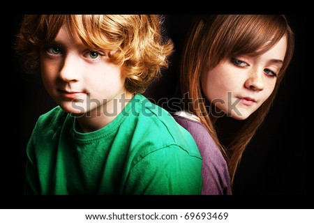 Brother and sister together in front of a black background. - stock photo