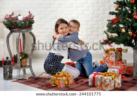 brother and sister under the Christmas tree with gifts