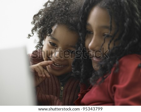 Brother and sister using a laptop - stock photo