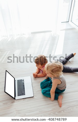 Brother and sister using laptop together - stock photo