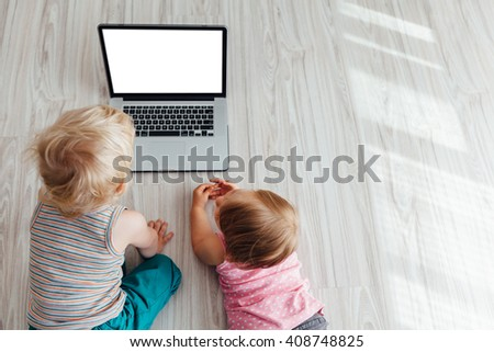 Brother and sister using laptop together with copy space - stock photo