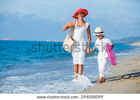 Brother and sister walking along a tropical beach