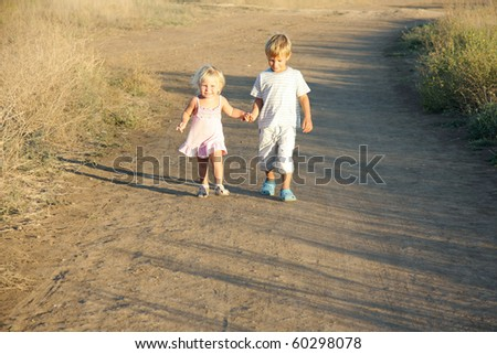 brother and sister walking by country road - stock photo