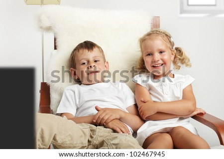Brother and sister watching TV at home