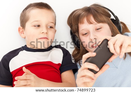 brother and sister watching  video on smart phone - stock photo