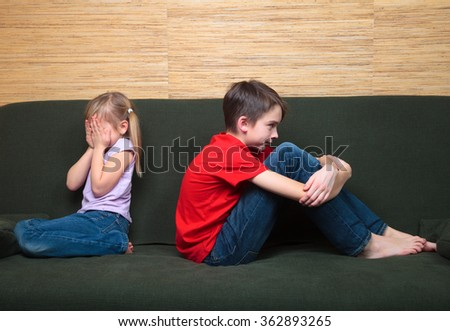 Brother and sister  wearing casual clothes  sitting on a green couch back to back arter fight. Girl covers her face with hands - stock photo