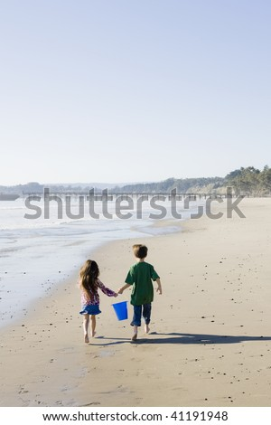 Brother and Sister with Bucket Running on the Beach - stock photo
