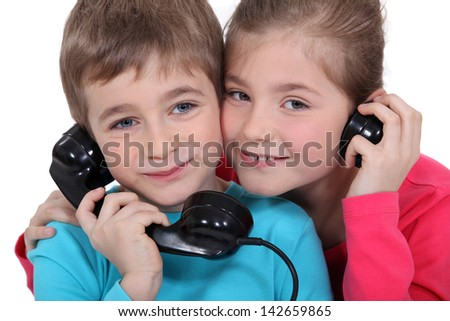 Brother and sister with old fashioned telephone - stock photo