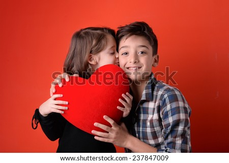 Brother and sister with red heart studio portrait against red background. - stock photo
