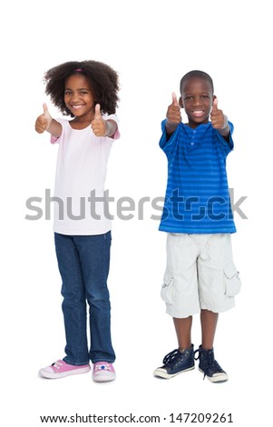 Brother and sister with thumbs up on a white background - stock photo
