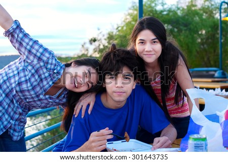 Brother and sisters outdoors in group hug, dining and hanging out - stock photo