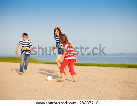 Brother and sisters play with a beach ball outdoors. Family fun concept